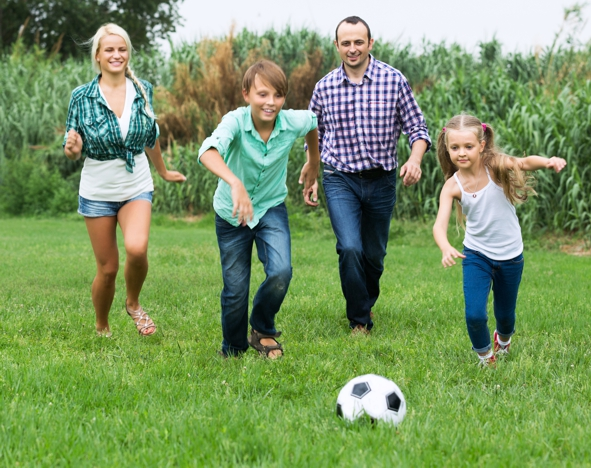 Cheerful happy children and parents running with ball at sunny day